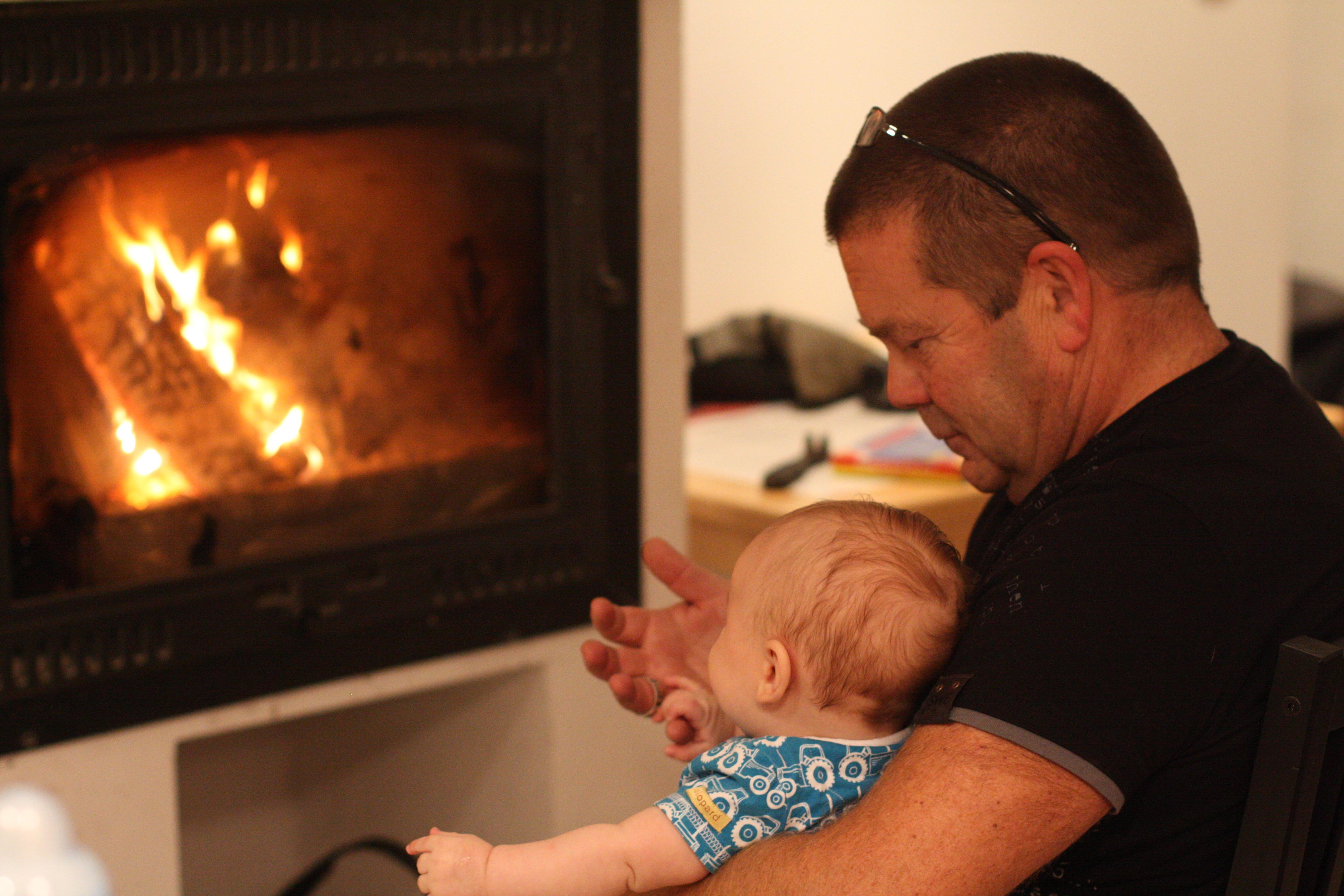 Sixten & Morfar betraktar brasan. Eld är förhäxande även för en 11 veckor gammal kille.